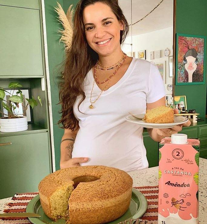 Chef Renata Vanzeto segurando um uma fatia de bolo de fubá com castanha